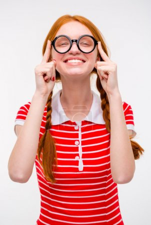 Cheerful funny young female fixing glasses and smiling
