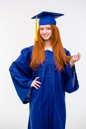 Beautiful young positive woman in graduation cap and gown