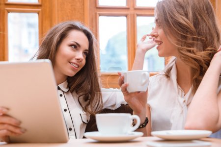 Photo for Portrait of a girlfriends drinking coffee and speaking in cafe - Royalty Free Image