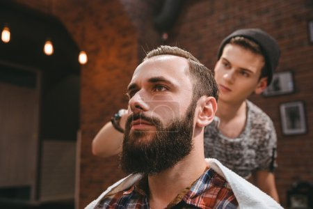 Modern barber combing hair of client with beard at barbershop
