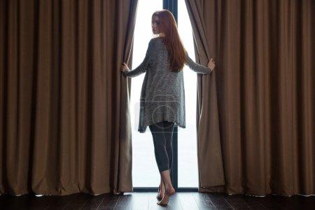 Photo pour Détendu belle rousse jeune femme ouvrant les rideaux, debout pieds nus devant la fenêtre et regardant en arrière - image libre de droit