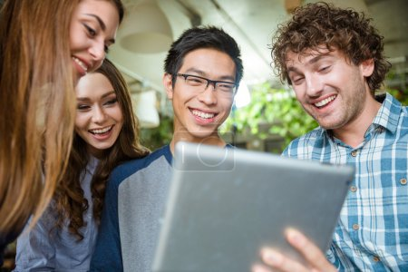Cheerful young people laughing and using tablet
