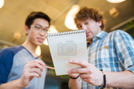 Photo pour Étudiant montrant ses notes dans un bloc-notes à son ami - image libre de droit