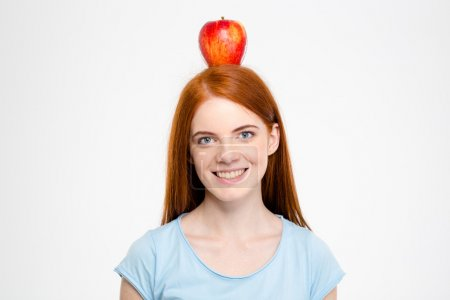 Smiling redhead woman standing with apple on head