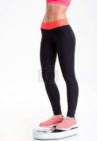 Photo pour Plan rapproché de belles jambes minces de femme de forme physique dans les leggings noirs restant sur l'échelle de pesage au-dessus du fond blanc - image libre de droit
