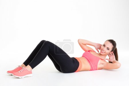 Cheerful attractive young sportswoman doing exercises lying on the floor