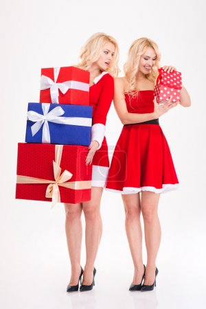 Two sisters twins in santa costumes holding and opening presents
