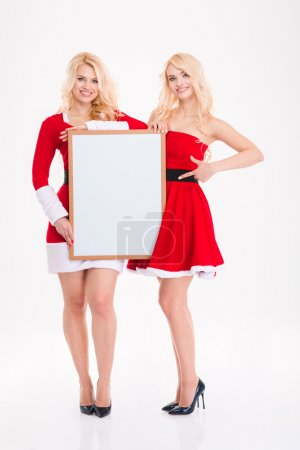 Sisters twins in red santa claus dresses with blank board
