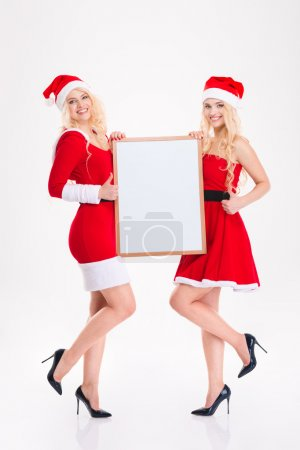 Charming young sisters twins with blank board showing thumbs up