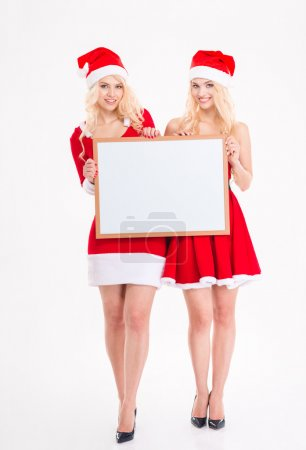 Two cheerful sisters twins posing with blank board