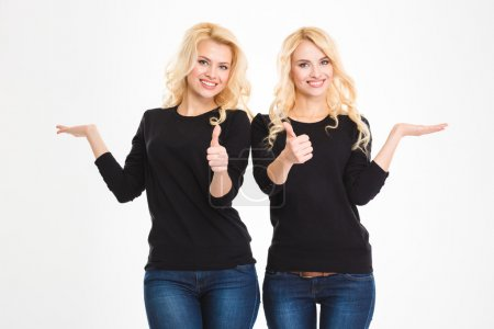 Sisters twins showing thumbs up