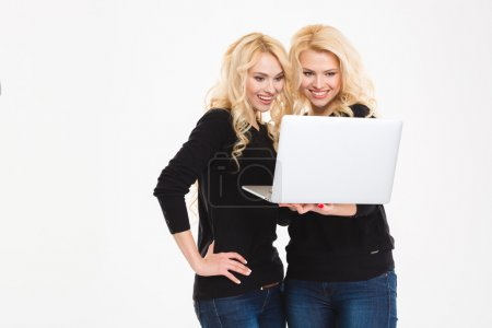Happy sisters twins using laptop computer