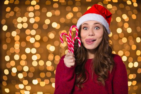 Funny cute girl in santa claus hat with christmas lollypops