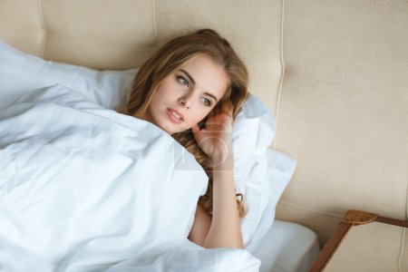 Relaxed attractive young woman waking up in bed
