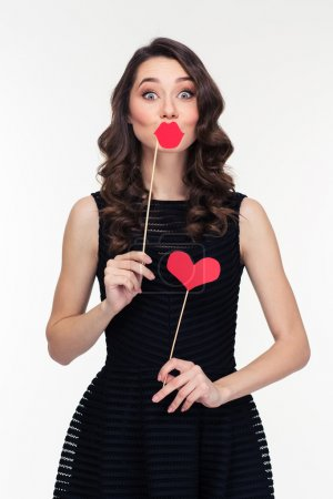 Funny female using fake lips and heart props on sticks