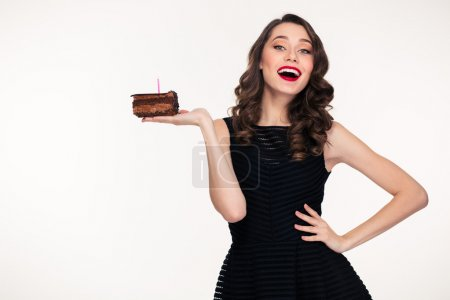 Cheerful woman holding piece of chocolate birthday cake with candle