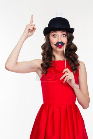 Playful woman having fun with moustache props