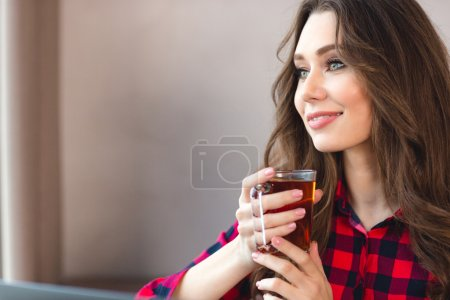 Thoughtful happy woman holding glass with tea