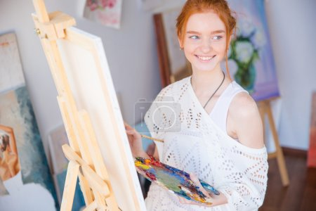 Woman painter holding palette with oil paints in art studio