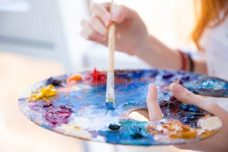 Photo pour Gros plan de pinceau dans les mains de la femme mélangeant les peintures sur la palette - image libre de droit