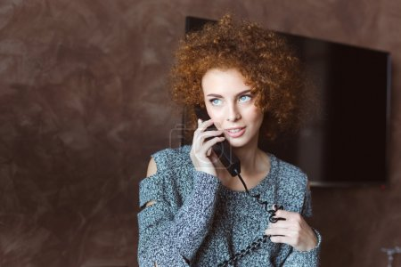 Portrait of pretty smiling redhead curly young female using telephone