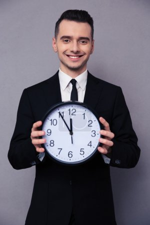 Smiling businessman holding wall clock