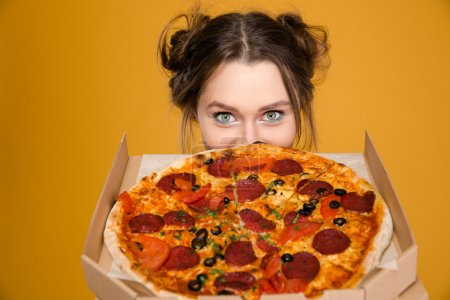 Lovely cute positive young woman hiding behind pizza