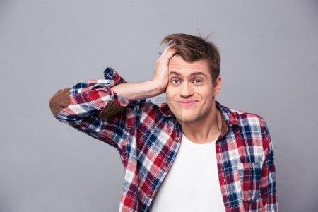 Photo pour Gros plan d'un jeune homme embarrassé en chemise à carreaux se grattant la tête et regardant confus sur fond gris - image libre de droit