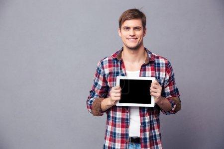 Šťastný atraktivní muž v kostkované košili drží prázdnou obrazovku tabletu