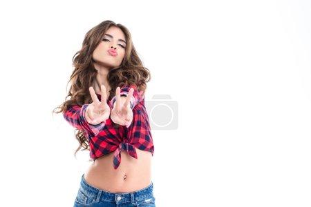 Photo pour Mignon belle jeune femme montrant signe de paix avec les deux mains et l'envoi d'un baiser sur fond blanc - image libre de droit