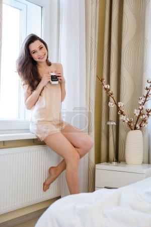 Photo pour Belle jeune femme heureuse en lingerie assise sur le rebord de la fenêtre et boire du café à la maison - image libre de droit