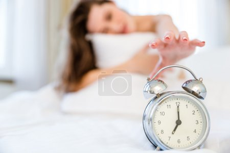 Woman trying to turn off the alarm clock