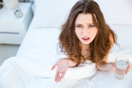 Woman sitting on bed with pills and glass of water