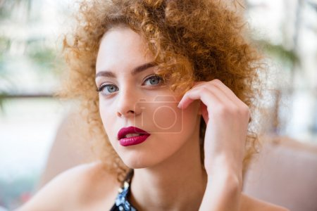 Redhead woman with curly hair looking at camera