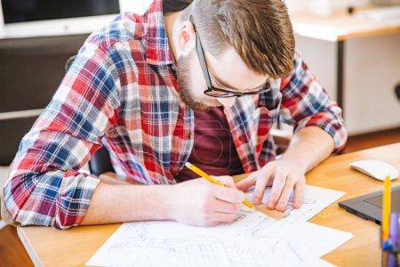Photo pour Étudiant travailleur sérieux avec la barbe dans les lunettes assis au bureau et dessin plan directeur - image libre de droit