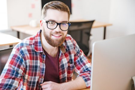 Happy handsome young man sitting and working with computer