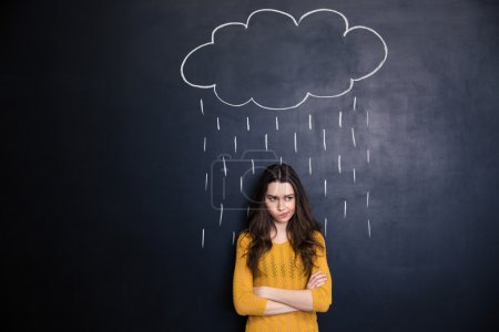 Unpleased woman with raincloud drawn over her on blackboard background