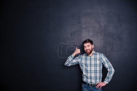 Photo for Smiling casual man showing thumb up over black background - Royalty Free Image