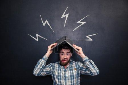 Photo pour Drôle choqué jeune homme tenant un ordinateur portable au-dessus de sa tête imitant le toit et se cachant des éclairs dessinés sur fond de tableau - image libre de droit