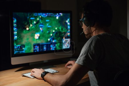 Photo for Back view of concentrated young gamer in headphones and glasses using computer for playing game at home - Royalty Free Image