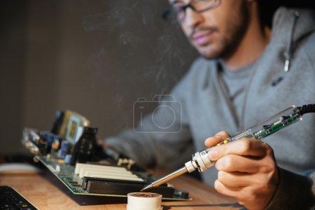 Photo pour Gentil jeune homme à capuche et lunettes à l'aide de fer à souder pour la réparation des motheboard - image libre de droit