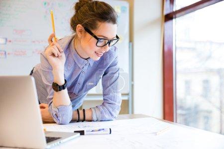 Photo pour Heureuse jeune à lunettes, debout près de la fenêtre au bureau et en collaboration avec plan - image libre de droit