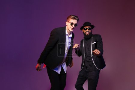 Photo for Two attractive cheerful young men in sunglasses dancing over purple background - Royalty Free Image