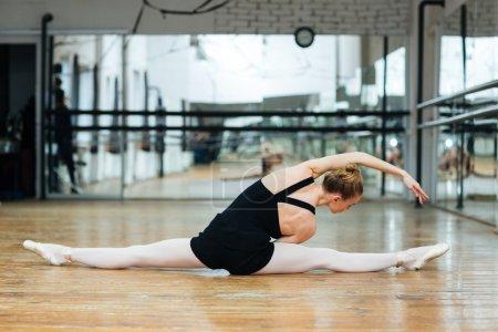 Photo pour Ballerine, faire des étirements exerce sur le sol dans les cours de danse classique - image libre de droit