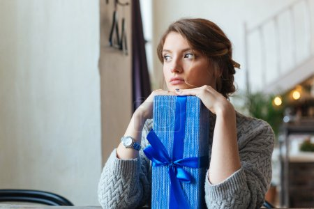 Woman sitting at the table with gift box