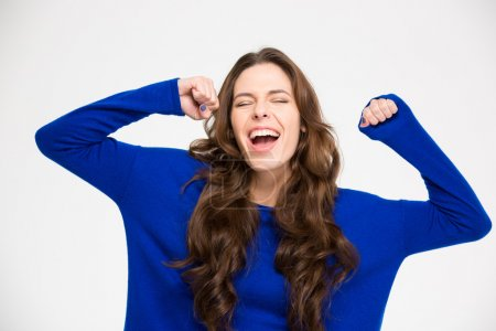 Ecstatic excited successful young woman with raised hands celebrating victory