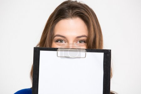 Cute lovely young woman hiding behind blank clipboard