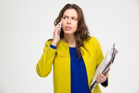 Pensive unpleased young woman with clipboad talking on mobile phone