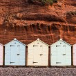 Beach hut row in pastel colors, red rock backgroun...