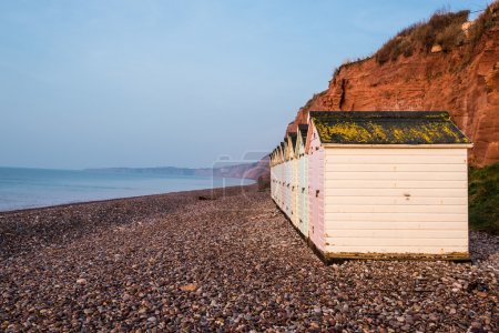 Beach hut row in pastel colors, red rock cliff bac...